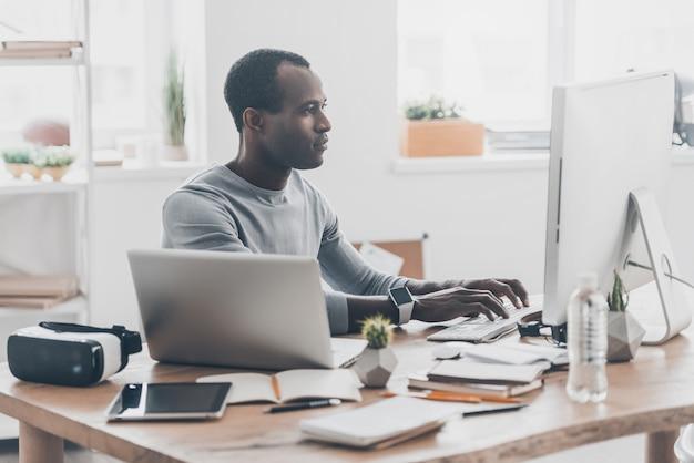 Полная концентрация. красивый молодой африканский человек работает на компьютере и улыбается, сидя на своем рабочем месте в творческом офисе