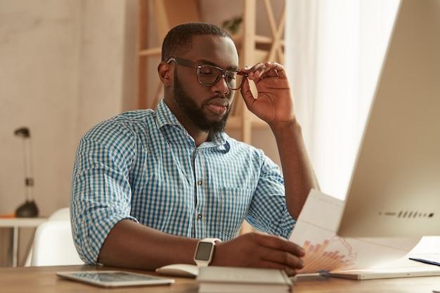 앉아있는 동안 컴퓨터에서 작업하는 안경에 전체 집중 똑똑한 젊은 아프리카 계 미국인 남자