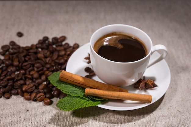 Полная чашка темного кофе в чашке белого цвета слоновой кости рядом с палочками корицы и листьями мяты с фасолью на заднем плане на скатерти