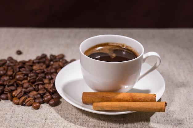 テーブルクロスの背景にシナモンスティックと豆の横にある白いティーカップとソーサーのダークコーヒーのフルカップ