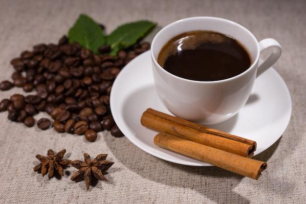 テーブルクロスの背景にシナモンスティック、スパイス、ミントの葉、豆の横にある白いティーカップとソーサーのダークコーヒーのフルカップ