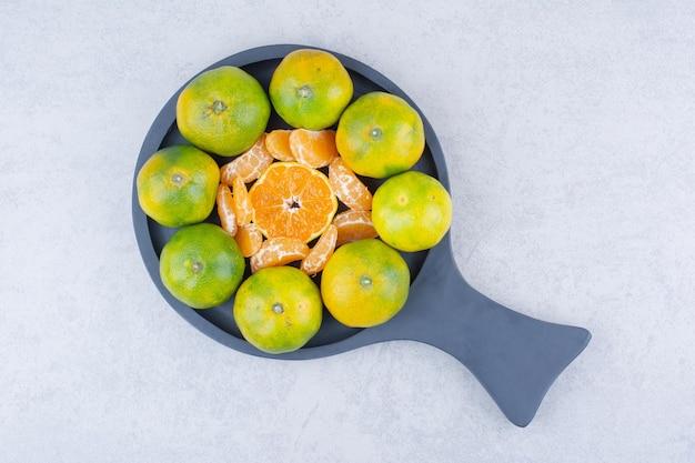 Padella scura piena di mandarini acidi su bianco