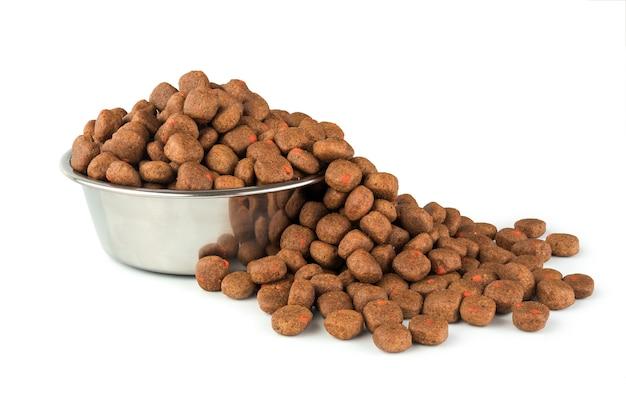 ペットショップについてのデザインのための白い背景のステンレス皿の上の完全な犬または猫の食べ物。動物とペットのコンセプト。
