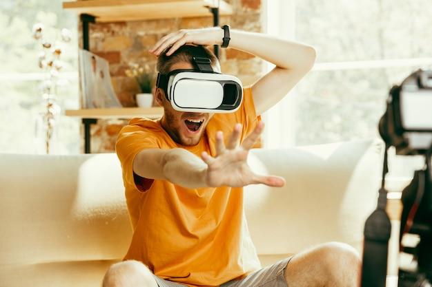 Pieno di emozioni. blogger maschio caucasico con revisione video di registrazione della fotocamera professionale