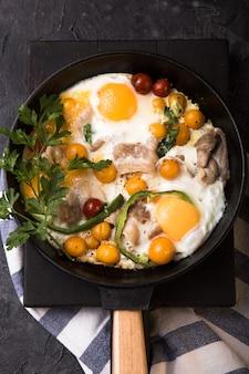 Full english breakfast   fried egg, tomato, bacon,  dish in iron frying pan.