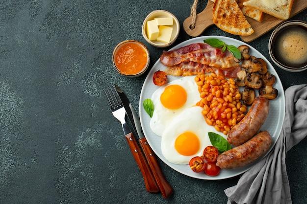 Полный английский завтрак на тарелке с яичницей