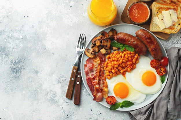 Full english breakfast on a plate with fried eggs, sausages, bacon, beans, toasts and coffee on light stone background. with copy space. top view.