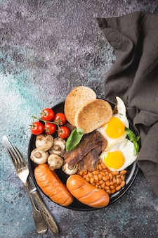 目玉焼き、ソーセージ、ベーコン、豆、トースト、トマトをダークストーンに乗せたフルイングリッシュブレックファースト