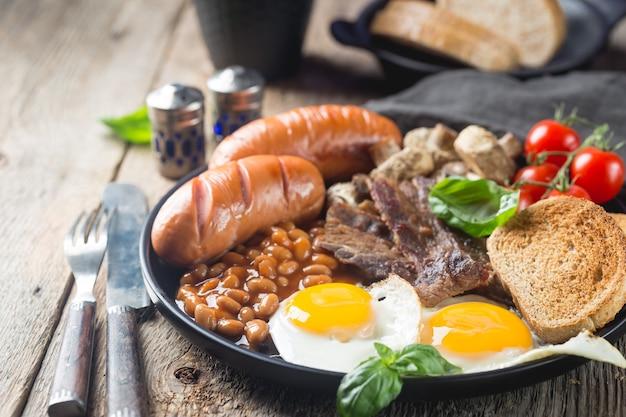 素朴な木製の目玉焼き、ソーセージ、ベーコン、豆、トースト、トマトのフルイングリッシュブレックファースト