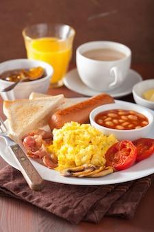 Полный английский завтрак с яичницей, беконом, колбасой, фасолью и помидорами