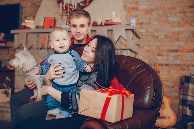 Full family sitting on a single sofa at christmas with a brown gift