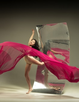 Full of feelings. modern ballet dancer on brown wall with mirror. illusion reflections on surface. magic of flexibility, motion with fabric. concept of creative art dancing, action, inspiring.