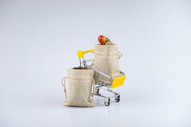 Полностью заполненные мешки с желудями и кофейными зернами, на тележке.