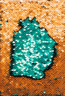 Full frame abstract background of green and golden reflective sequins