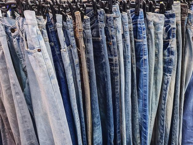 Full frame background of hanging denim jeans for sale