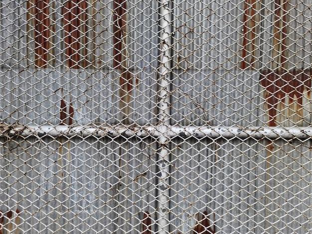 녹슨 물결 모양 아연 장에 대하여 철망사 벽의 전체 구조 배경
