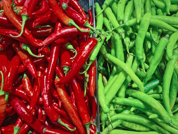 Full frame background of two halves of red and green chilies for sale