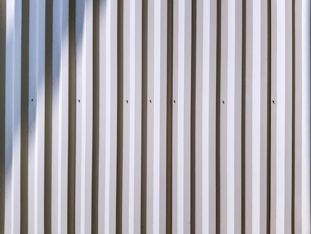 Full frame background of white corrugated wall with light and shadow