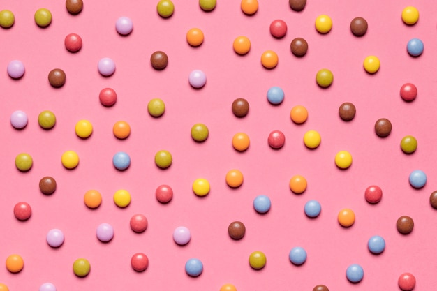 Full frame of colorful multicolored gem candies on pink background