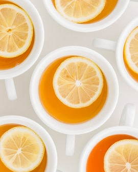 Full frame of lemon herbal tea in cups on white backdrop