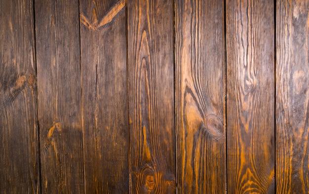 真上から撮影されたダークブラウンの木製床板のフルフレーム。木の結び目と板の間の隙間があります。