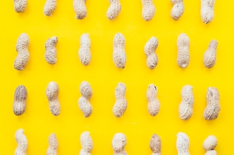 Full frame of raw whole peanuts on yellow backdrop