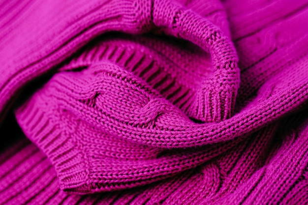 Full frame shot of knitted fabric magenta color background
