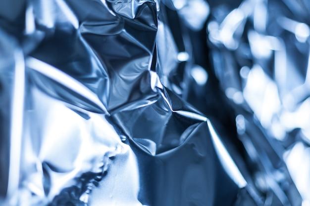 Full frame take of a sheet of crumpled blue aluminum foil