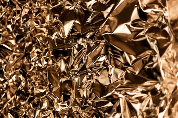 Full frame take of a sheet of crumpled gold aluminum foil