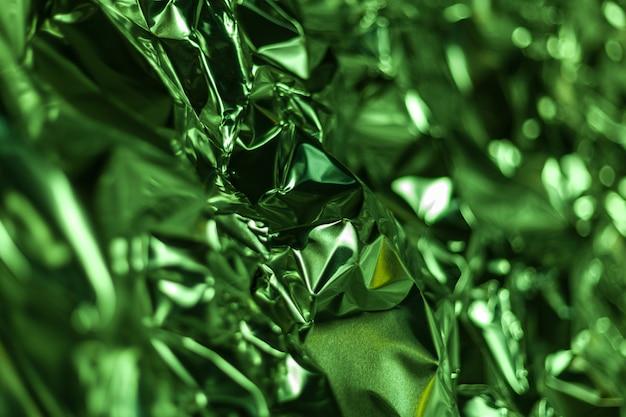 Full frame take of a sheet of crumpled green aluminum foil