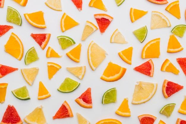 Full frame of triangular citrus fruits slices isolates on white background