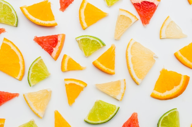 Full frame of triangular citrus fruits slices on white background