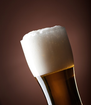 Full glass of beer on a brown