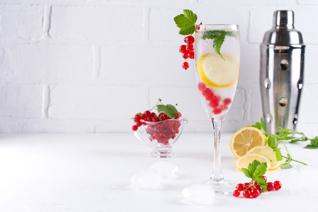 Full glass of cold refreshing  water with lemon and mint on white background