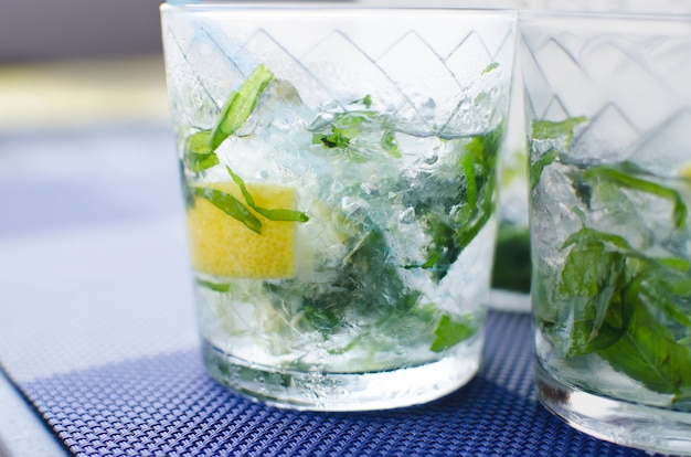 Full glass of fresh cool transparent water with ice, lemon and , basil leaves