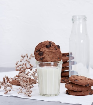 Full glass of milk and round chocolate chip cookies