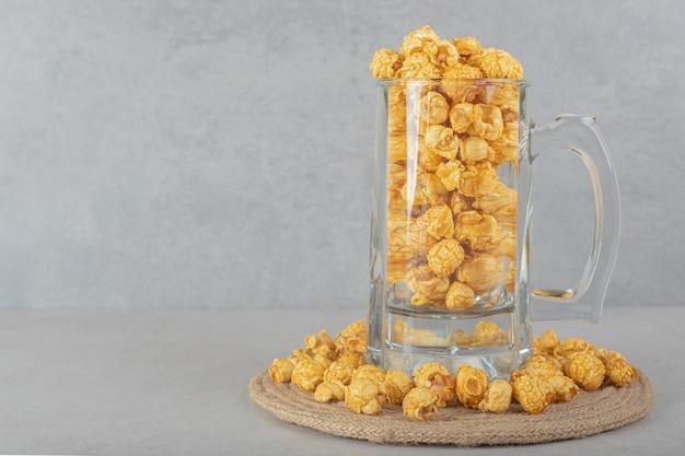 Tazza piena di vetro su un sottopentola inanellato con popcorn al gusto di caramello su un tavolo di marmo.