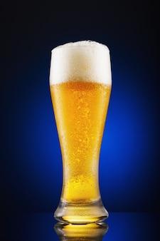 青い背景に注ぎたてのビールのフルグラス