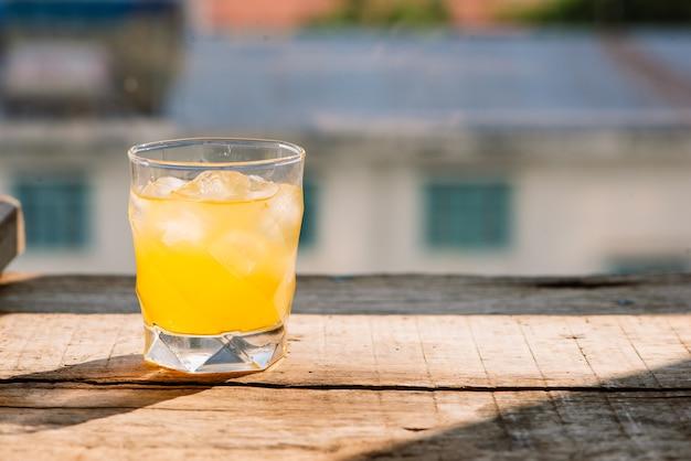 オレンジジュースのクローズアップの完全なガラス。夏の朝に焦点が合っていない正体不明のレストランの木製テーブルに新鮮なオレンジジュース