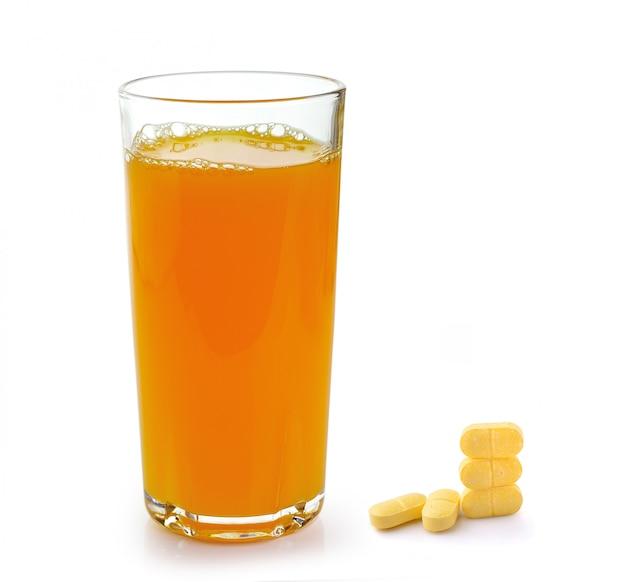 Full glass of orange juice and vitamin c pills isolated on white