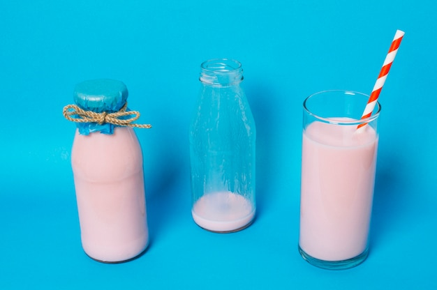 Full glass of pink smoothie next to empty and full bottles