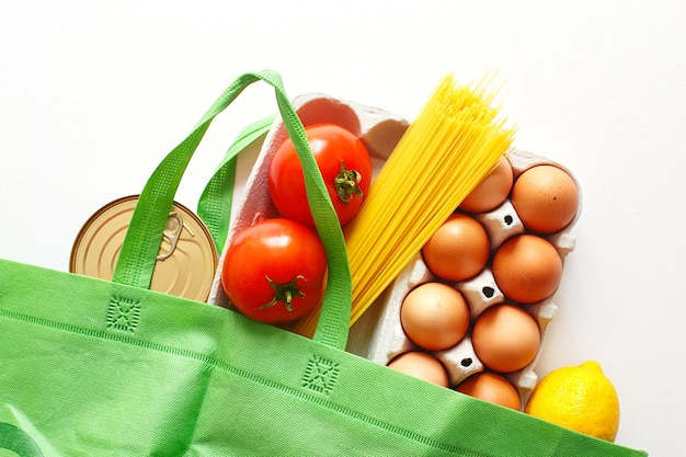 Full green bag of healthy food on a white background. top view. fruit, vegetable, eggs online shop. your text. food delivery