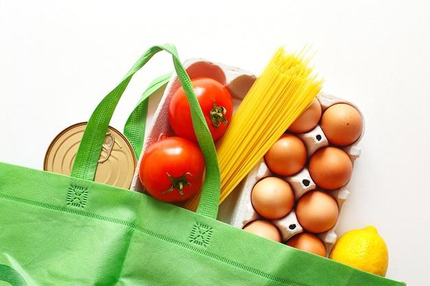 흰색 바탕에 건강 식품의 전체 녹색 가방. 평면도. 과일, 야채, 계란 온라인 상점. 당신의 텍스트. 음식 배달