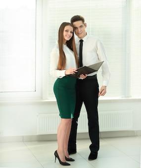 Полный рост. бизнес пара с буфером обмена, стоя в офисе.