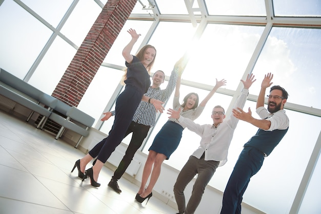 In full growth. cheering business team standing in the office.the concept of success