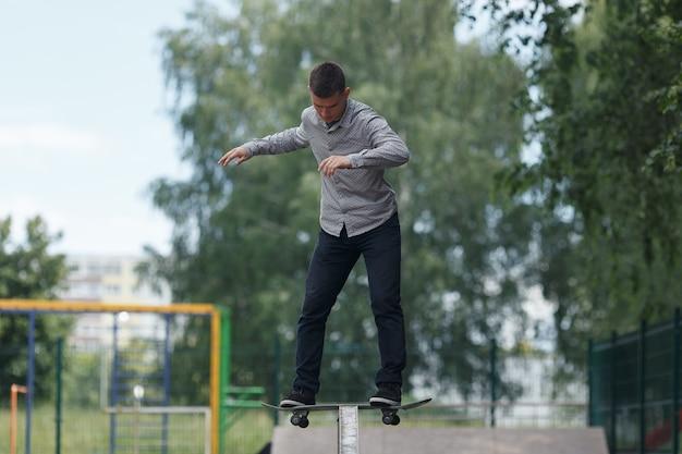 完全な成長ショット-かわいい若いブルネットのスケートボーダーは夏の日当たりの良い公園でスケートボードでトリックを示しています