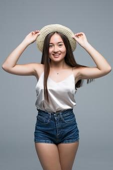 Ragazza asiatica a tutta altezza in cappello di paglia su sfondo grigio