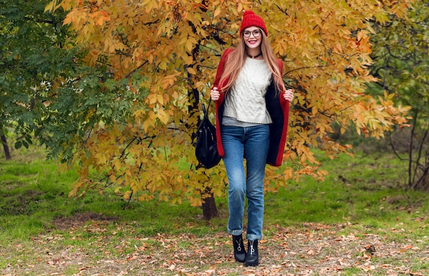 Full height autumn fashion image of pretty nice woman in red stylish coat and knitted hat, red lips posing on yellow park.