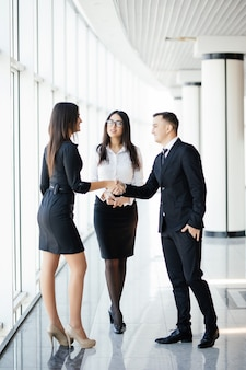 Full height businessman and businesswoman shaking hands in bright office