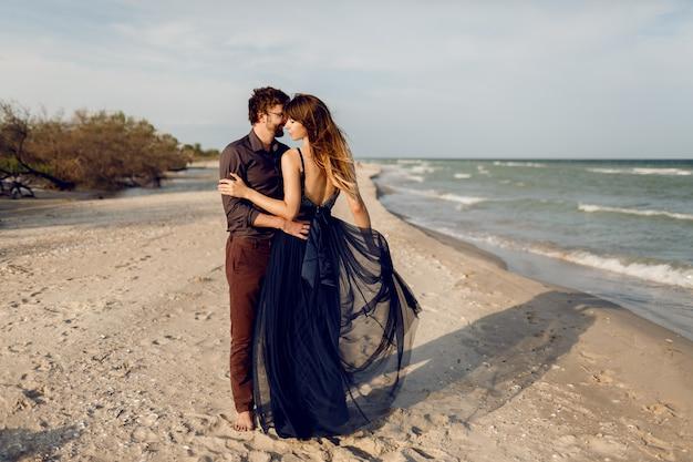 海の近くのイブニングビーチでロマンチックなカップルを受け入れる高さの完全なイメージ。優しさと彼女のボーイフレンドを抱き締める青いロングドレスの見事な女性。ハネムーン。